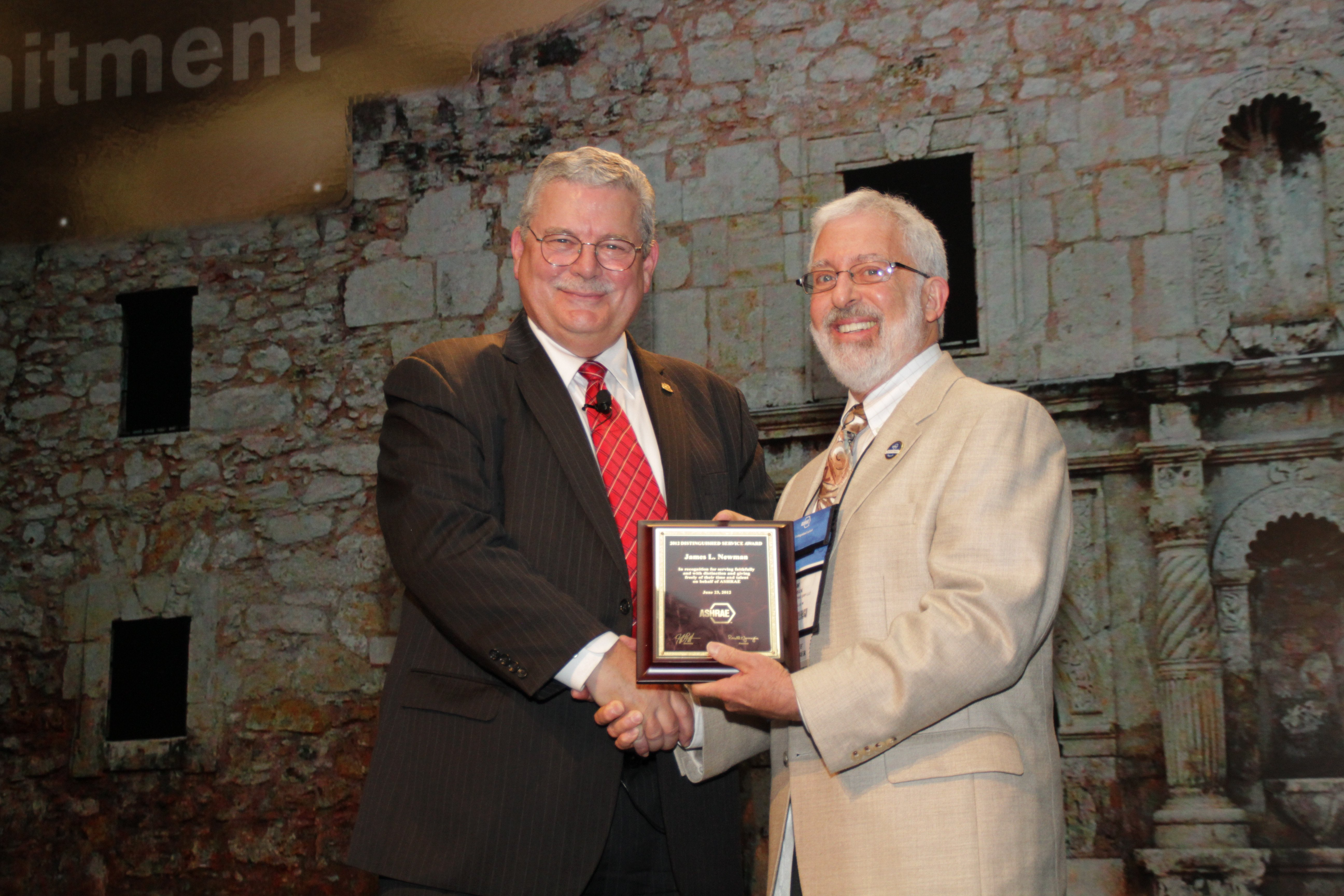 Ron Jarnagin (left), president of ASHRAE, congratulates Jim Newman on receiving the Distinguished Service Award at the ASHRAE Annual Conference.